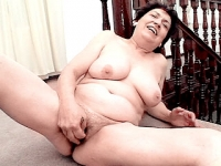 Mature brunette playing with her wet twat near the stairs